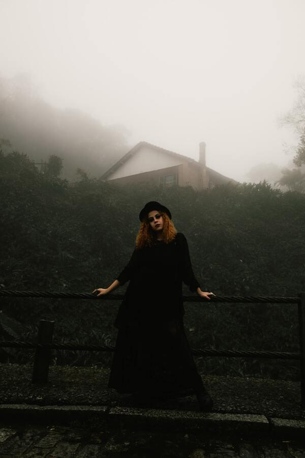 Garota usando vestido e chapéu preto com um muro de plantas ao fundo e uma casa coberta pla neblina