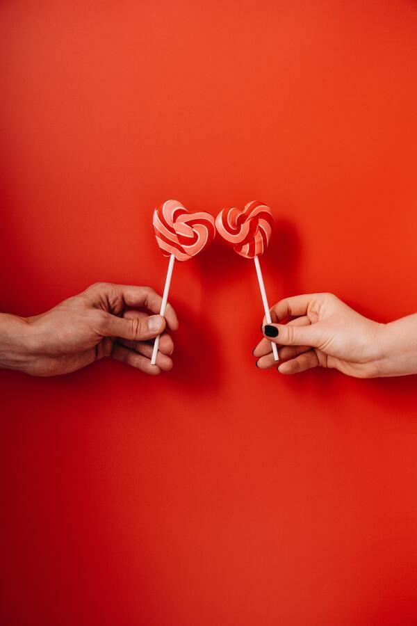 Duas mãos segurando pirulitos em formato de coração em um fundo vermelho