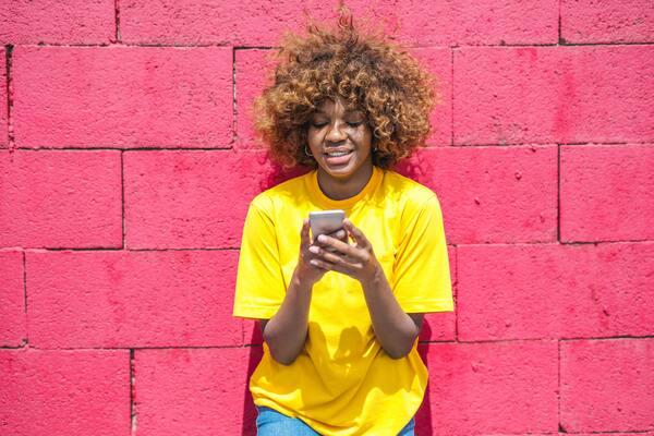 Uma garota negra de camiseta amarela segurando um celular numa parede vermelha ao fundo