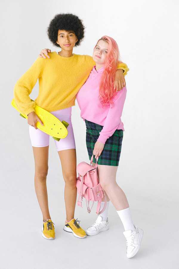 Uma garota negra usando uma blusa de tricô amarela abraçada ao lado de uma garota branca usando um moletom rosa