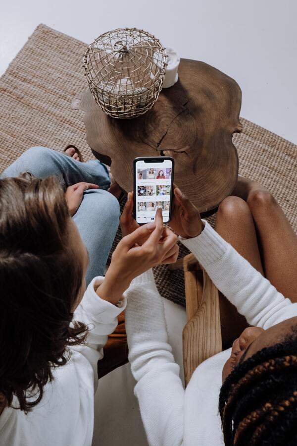Duas garotas segurando um celular com várias fotos na tela