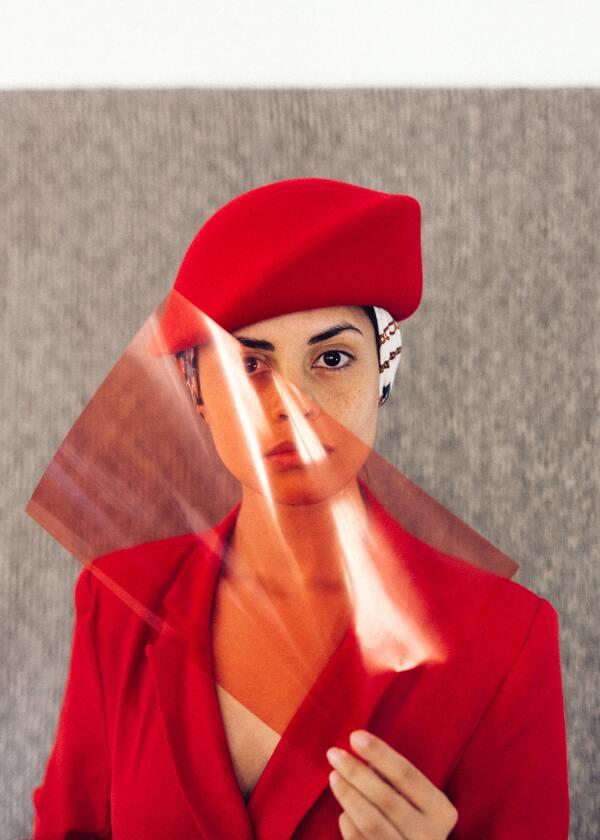 Mulher vestida de vermelho segurando um celofane da mesma cor