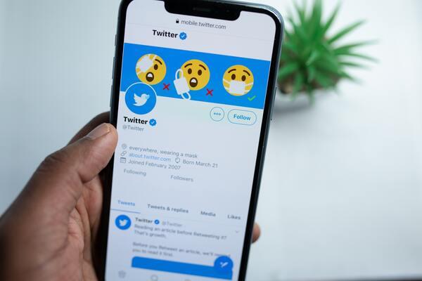 Uma mão segurando um smartphone mostrando a tela inicial do Twitter