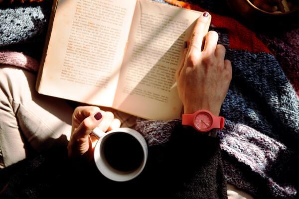 Um livro aberto no colo de uma pessoa segurando uma caneca branca de café
