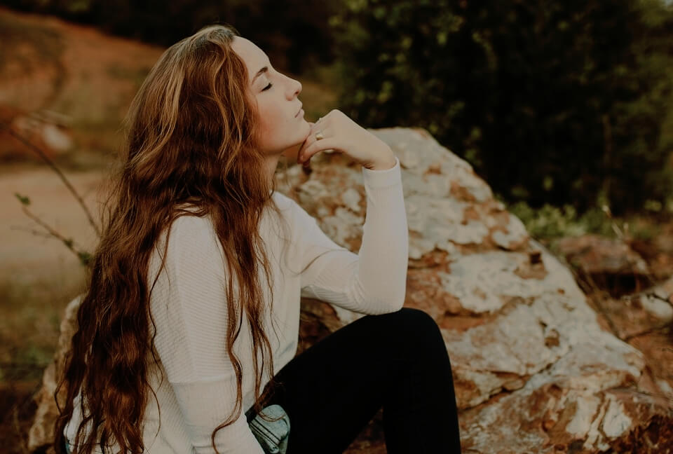 Sagittarius edit of a woman with long brown hair sitting on a rock
