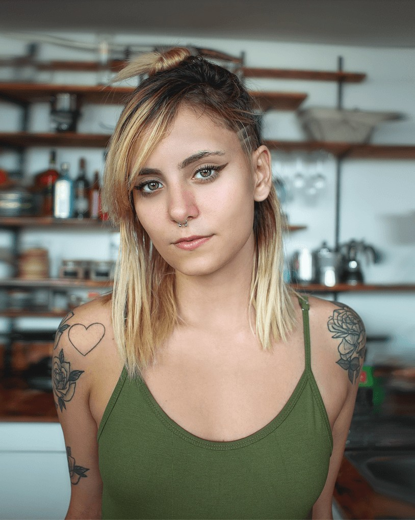 woman with tattoos wearing a green top