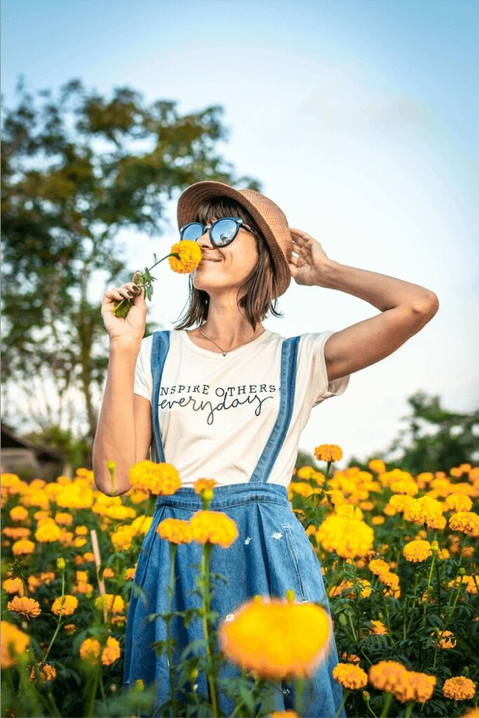 woman wearing a white tshirt and denim overalls smells a yellow flower