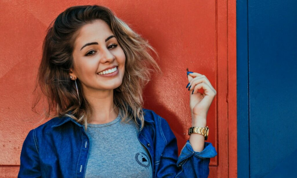 woman wearing a denim shirt smiling while standing in front of a red and blue wall