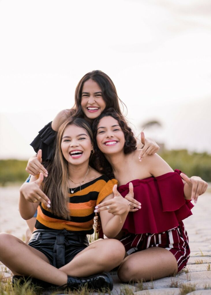 three smiling women taking a photo on the beach