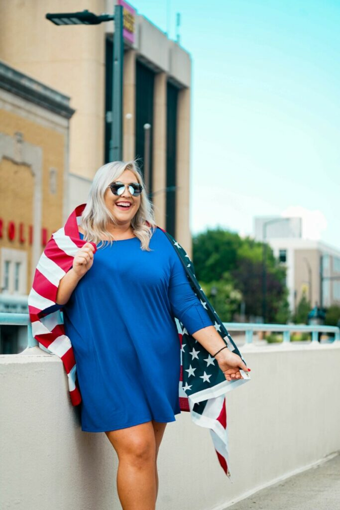 woman in blue dress and American flag celebrates July 4th