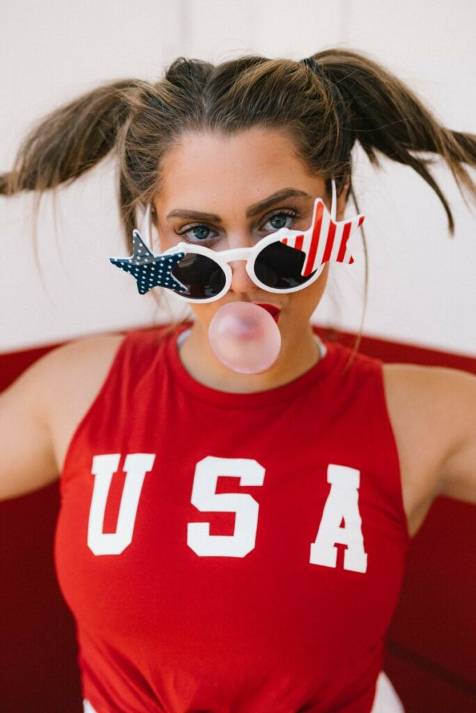 woman wearing July 4th outfit with stars and stripes sunglasses and USA shirt