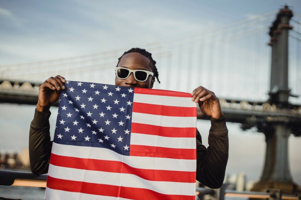 man holds up American flag on July 4th