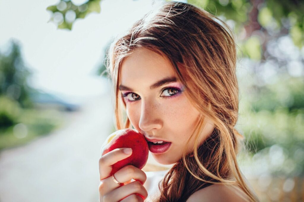 woman with Prism Makeup filter holding an apple