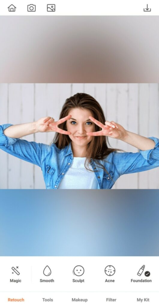 woman wearing chambray shirt making the peace sign over her eyes