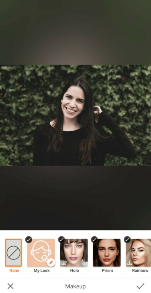 woman with dark hair and black sweater standing in front of greenery