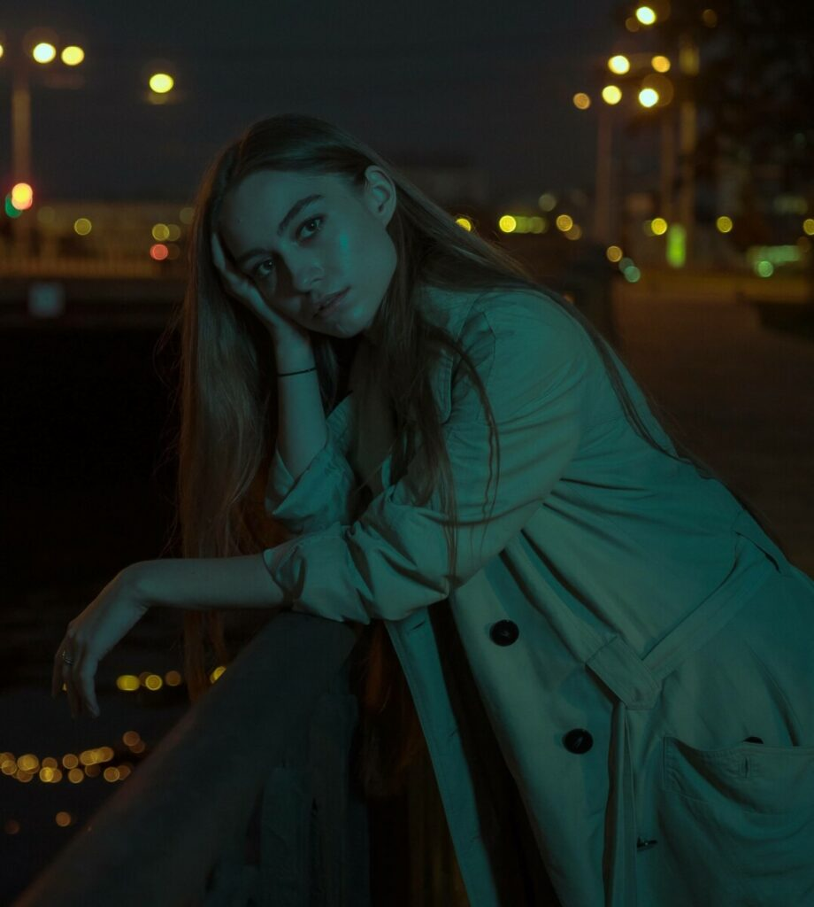 woman standing on a bridge at night