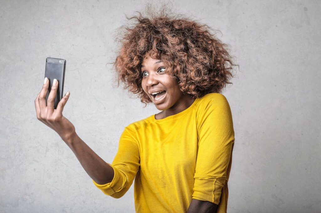 woman in yellow top takes a selfie