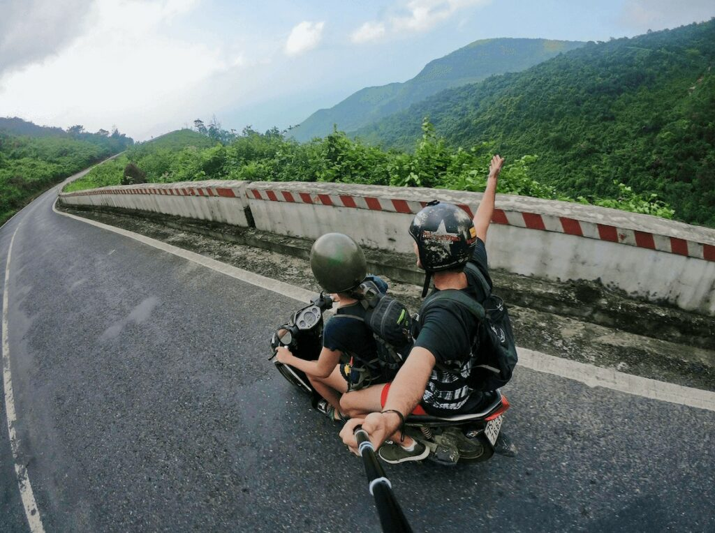 photo of two people riding a motorcycle