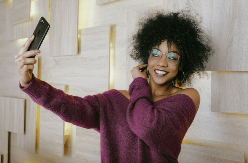 smiling woman in purple sweater takes a photo