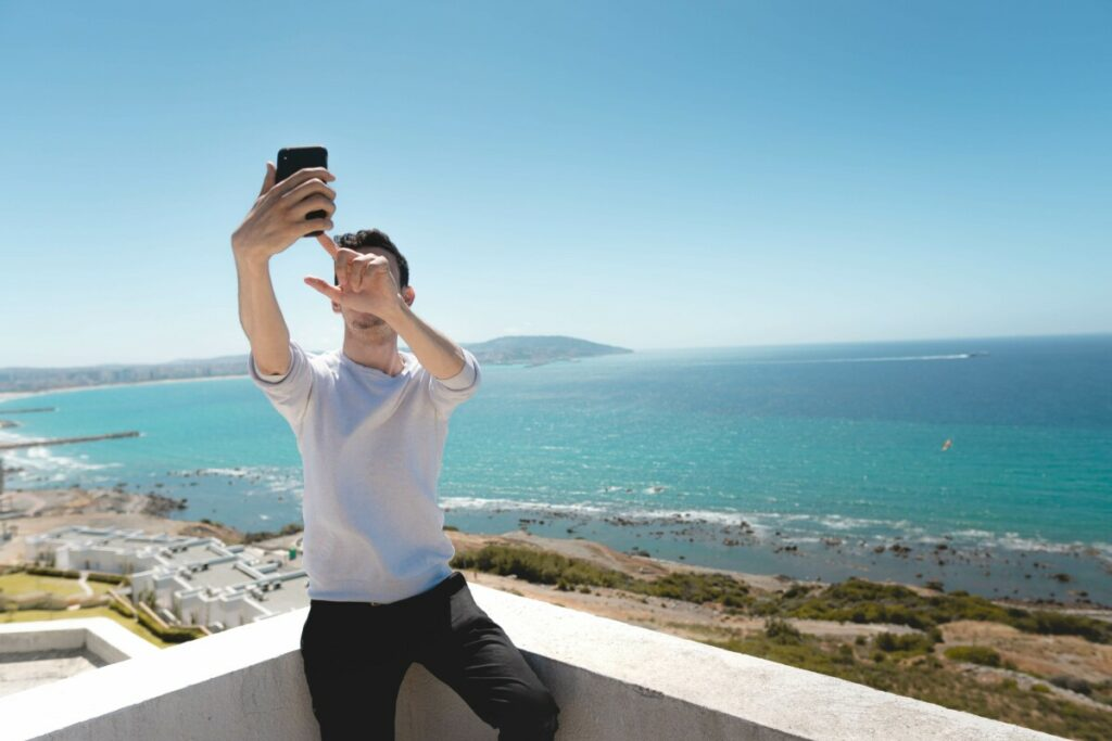 man takes photo in front an ocean view