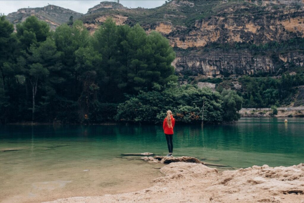 woman standing on the edge of a green lake