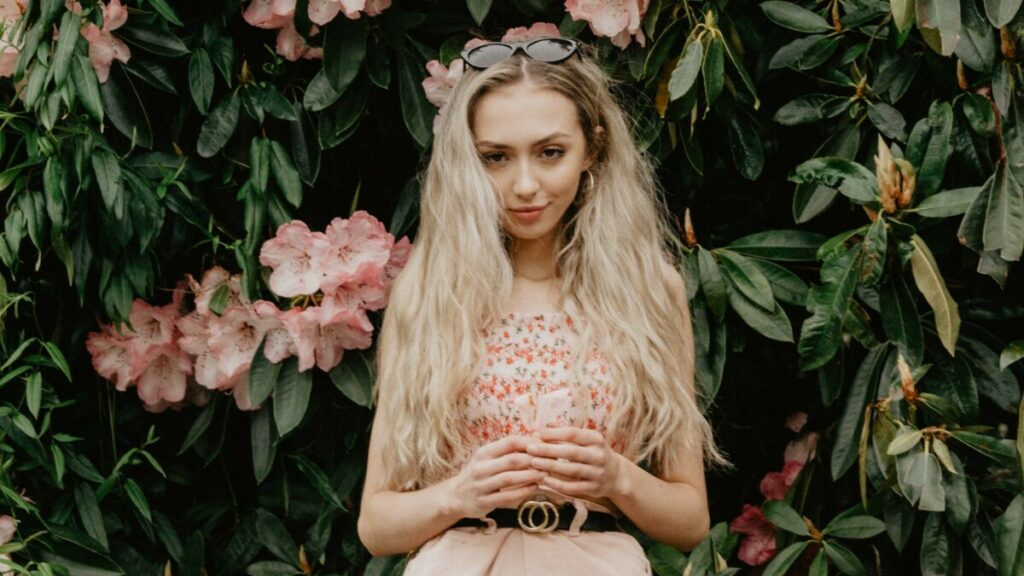 blonde woman standing in a garden