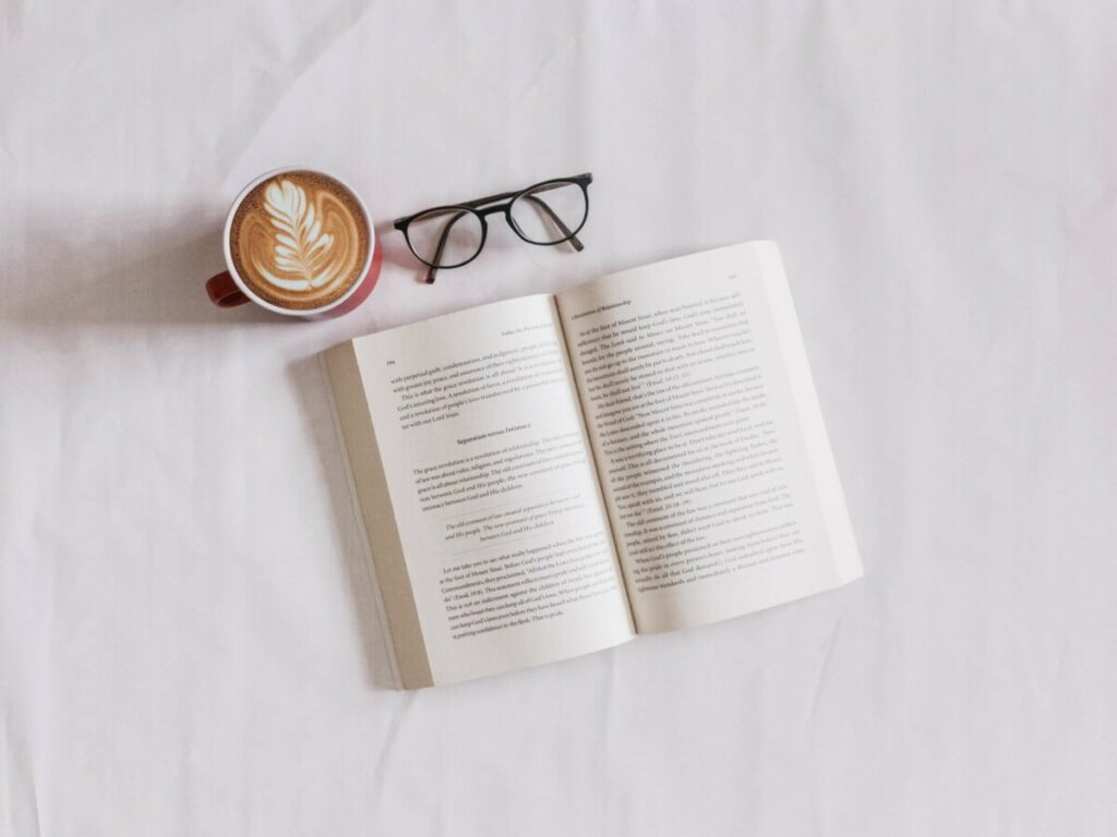 flat lay of an open book with coffee and reading glasses