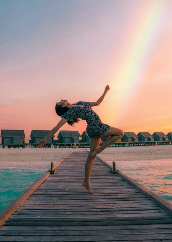 woman posing on a jetty at sunset with a rainbow in the sky