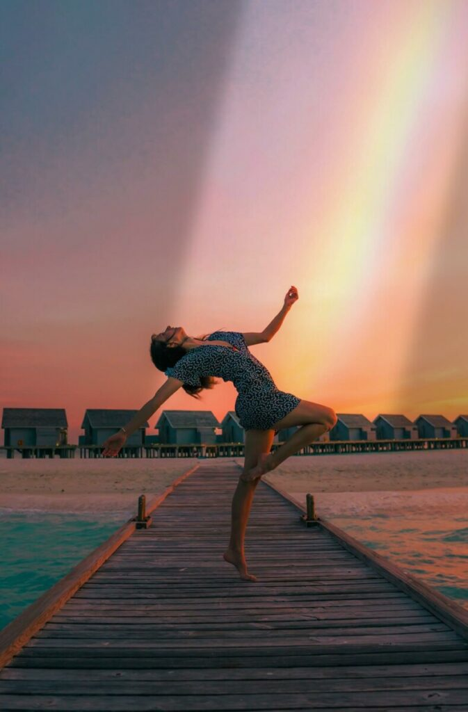 woman posing on a jetty with a rainbow in the sky
