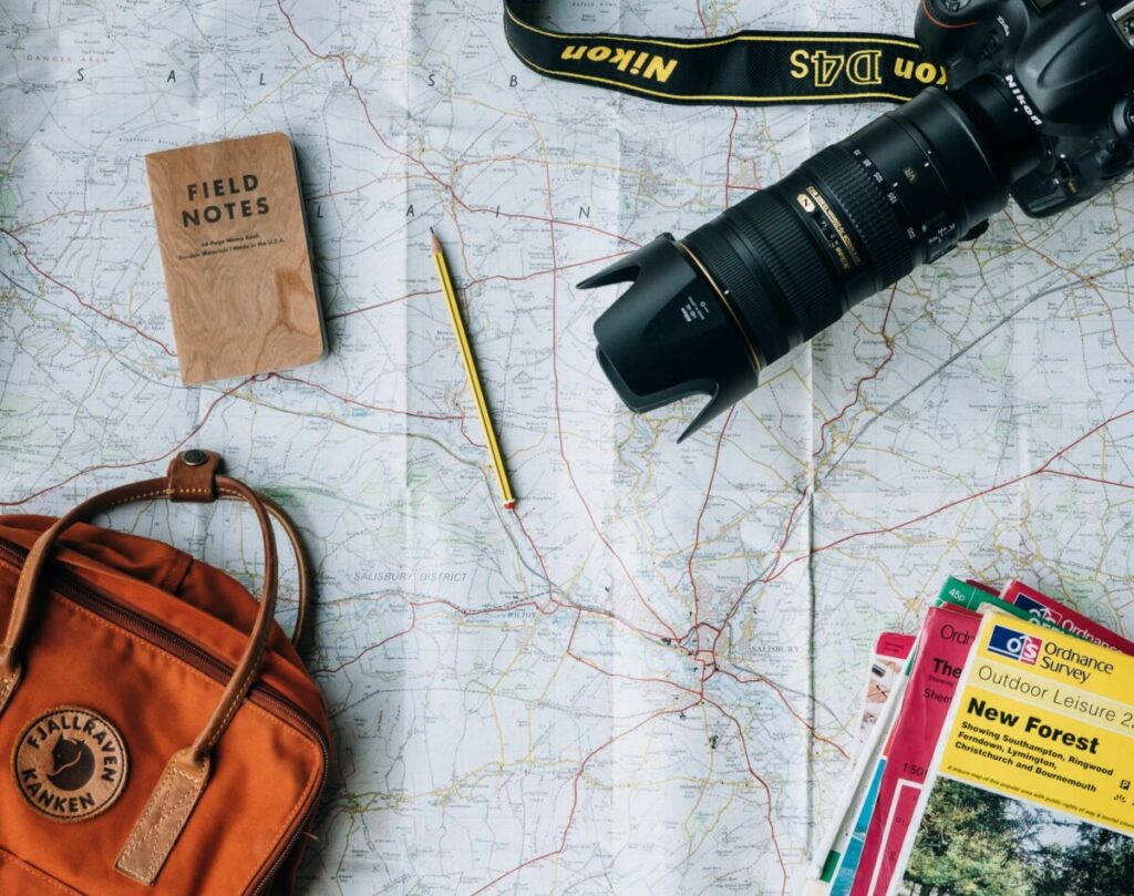 travel flat lay featuring a camera, backpack, notepad and map